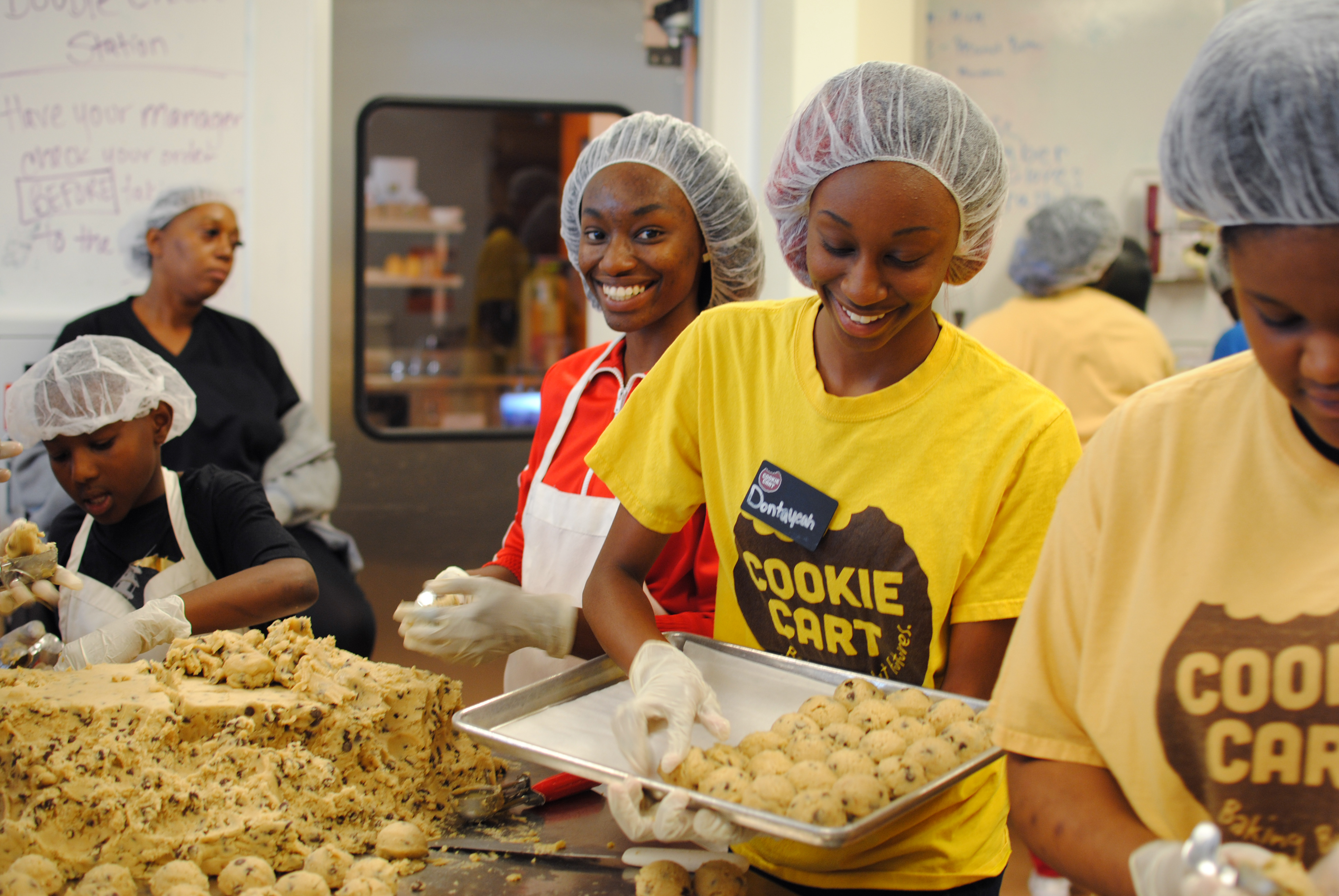 Group of teens from Northside Achievement Zone (NAZ) baking cookies with Cookie Cart