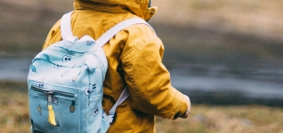 Young child wearing a yellow rain coat going to school