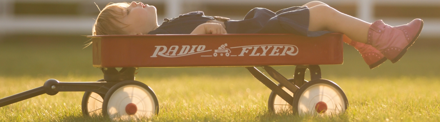 Little girl lying in a radio flyer wagon