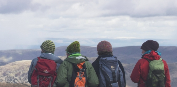 4 young people looking over the summit