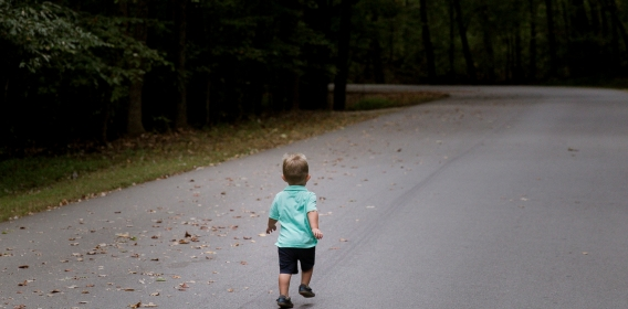 Little boy running down a road